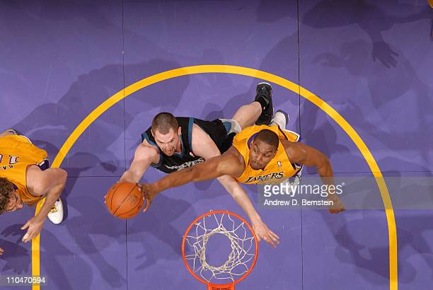 Andrew Bynum of the Los Angeles Lakers blocks the shot of Kevin Love of the Minnesota Timberwolves at Staples Center on March 18 2011 in Los Angeles...