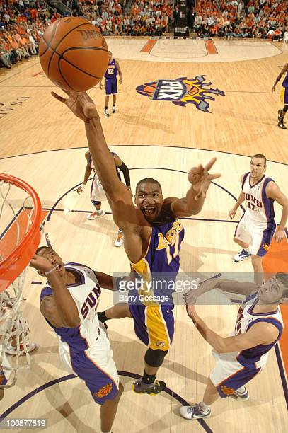 Andrew Bynum of the Los Angeles Lakers drives for a shot between Channing Frye and Goran Dragic of the Phoenix Suns in Game Four of the Western...