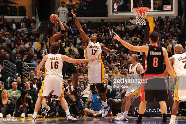 Andrew Bynum of the Los Angeles Lakers rises to contest the shot of Chris Bosh of the Toronto Raptors at Staples Center on November 30 2008 in Los...