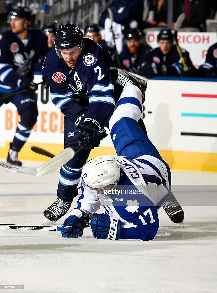 Andrew Campbell #2 of the Toronto Marlies takes a hit from Andrew MacWilliam #2 of the Manitoba Moose during opening night AHL game action on October 9, 2015 at the Ricoh Coliseum in Toronto, Ontario, Canada.