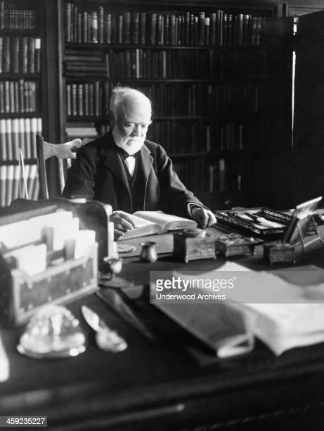 Andrew Carnegie reading a book at his desk New York New York April 5 1913