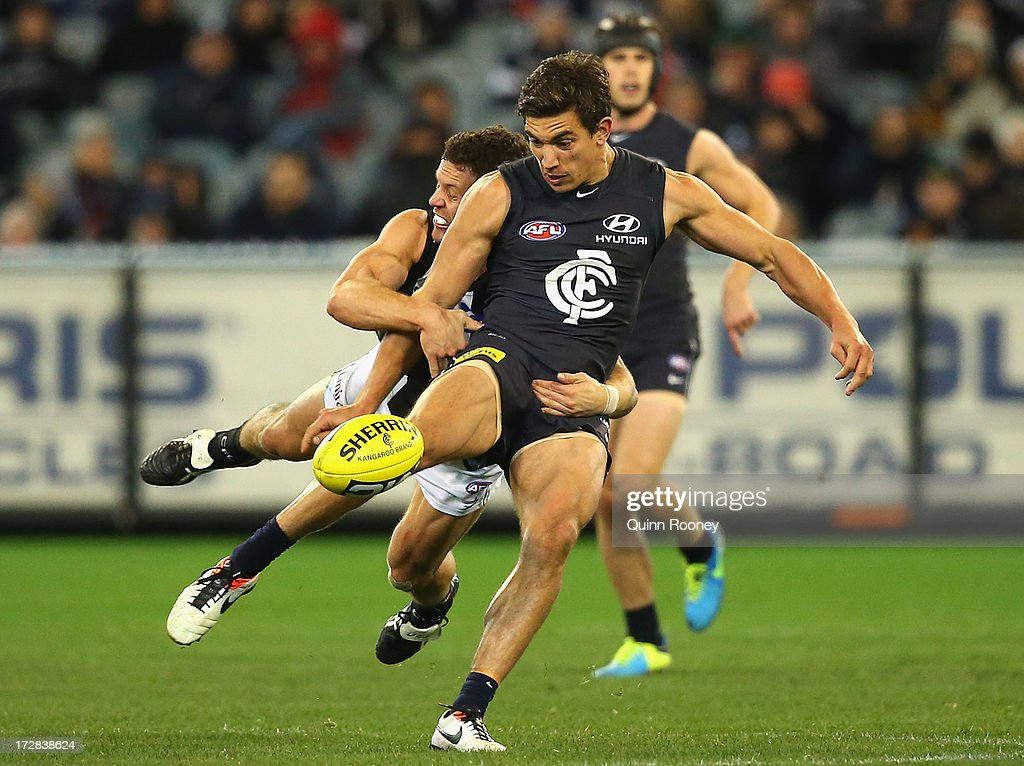 Andrew Carrazzo of the Blues kicks whilst being tackled by Luke Ball of the Magpies during the round 15 AFL match between the Carlton Blues and the Collingwood Magpies at Melbourne Cricket Ground on July 5, 2013 in Melbourne, Australia.