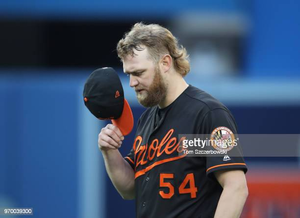 Andrew Cashner of the Baltimore Orioles reacts in the third inning during MLB game action against the Toronto Blue Jays at Rogers Centre on June 8...