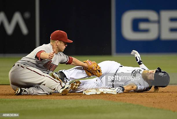 Andrew Cashner of the San Diego Padres is tagged out by Aaron Hill of the Arizona Diamondbacks as he's caught off of second base during the third...