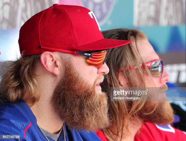 Andrew Cashner of the Texas Rangers and AJ Griffin of the Texas Rangers talk in the dugout during a game against the Los Angeles Angels of Anaheim at...