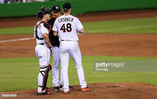 Andrew Cashner talks with Miami Marlins pitching coach Juan Nieves and catcher JT Realmuto during the third inning of the game against the Atlanta...