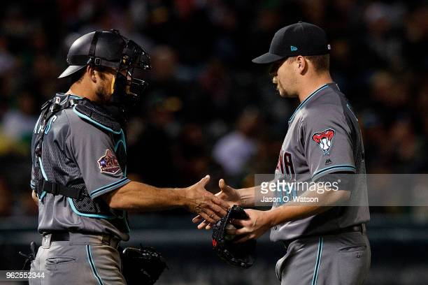 Andrew Chafin of the Arizona Diamondbacks celebrates with Jeff Mathis after the game against the Oakland Athletics at the Oakland Coliseum on May 25...