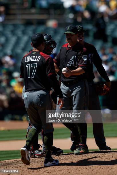Andrew Chafin of the Arizona Diamondbacks is relieved by manager Torey Lovullo during the seventh inning against the Oakland Athletics at the Oakland...