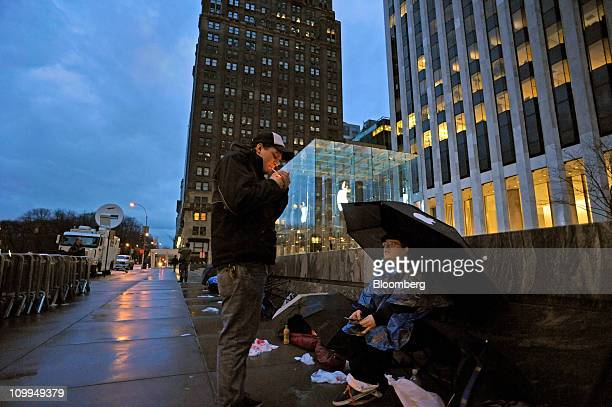 Andrew Christian right chats with another person in line as they wait in front of the Apple store on Fifth Avenue in the early morning hours to...