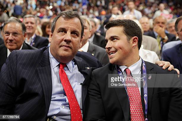 Andrew Christie speaks with his father New Jersey Gov Chris Christie while attending the first day of the Republican National Convention along with...