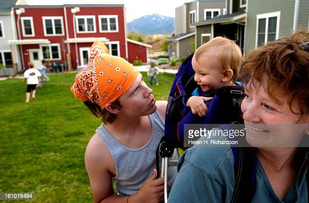 Andrew Clymer <cq> 15 <cq> left tries to get his 1 year old cousin Livia <cq> Hoskin <cq> to smile while Clymer's aunt Karin Hoskin <cq> smiles...