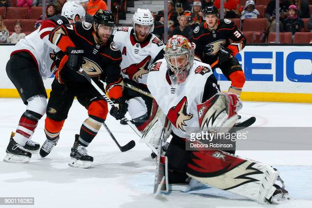 Andrew Cogliano and Jakob Silfverberg of the Anaheim Ducks battle for the puck against Alex Goligoski and Antti Raanta of the Arizona Coyotes during...