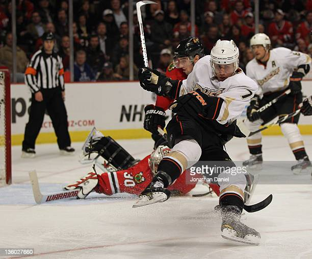 Andrew Cogliano of the Anaheim Ducks slips down on the ice after trying to get off a shot against Ray Emery of the Chicago Blackhawks after being...