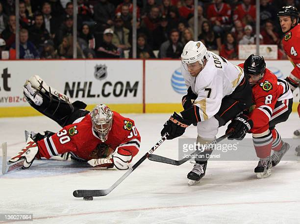 Andrew Cogliano of the Anaheim Ducks tries to shoot against Ray Emery of the Chicago Blackhawks as Nick Leddy hooks him from behind at the United...