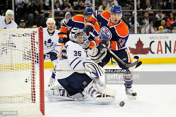 Andrew Cogliano of the Edmonton Oilers looks for the loose puck in front of goalie Vesa Toskala of the Toronto Maple Leafs in the second period...