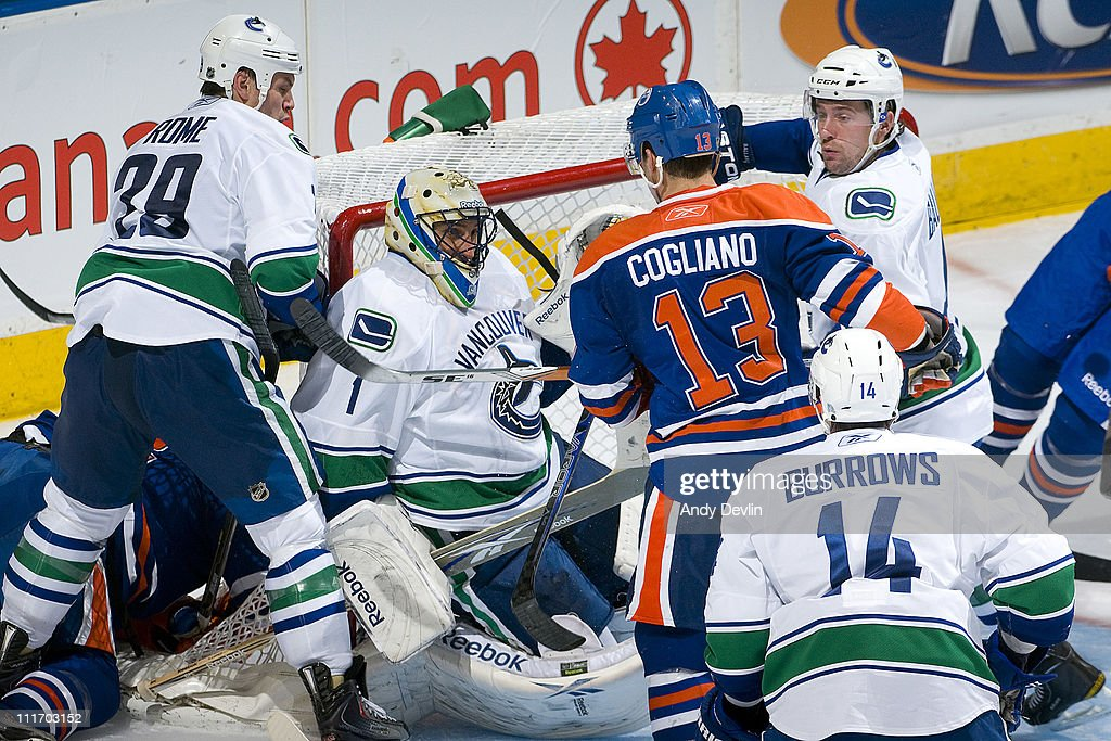 Andrew Cogliano #13 of the Edmonton Oilers looks for the puck in a crowd in front of Roberto Luongo #1 of the Vancouver Canucks at Rexall Place on April 5, 2011 in Edmonton, Alberta, Canada.