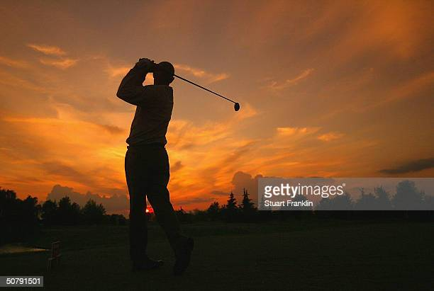 Andrew Coltart of Scotland plays his tee shot into the setting sun on the 10th hole during the rain delayed second round at The Telecom Italian Open...