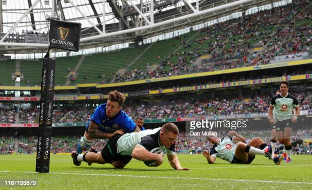 Andrew Conway of Ireland dives over to score his side's third try as he is tackled by Matteo Minozzi of Italy during the Guinness Summer Series match...