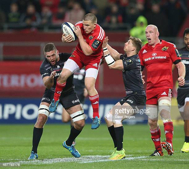 Andrew Conway of Munster catches the ball as Will Fraser and David Strettle challenge during the European Rugby Champions Cup match between Munster...