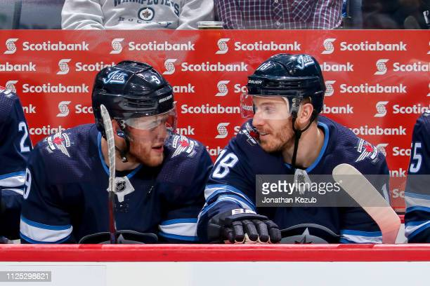Andrew Copp and Bryan Little of the Winnipeg Jets chat on the bench prior to puck drop against the Ottawa Senators at the Bell MTS Place on February...