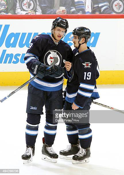 Andrew Copp and Nic Petan of the Winnipeg Jets discuss strategy during a second period stoppage in play against the Minnesota Wild at the MTS Centre...