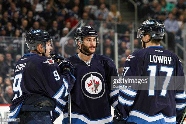 Andrew Copp Anthony Peluso and Adam Lowry of the Winnipeg Jets discuss strategy during a third period stoppage in play against the Columbus Blue...