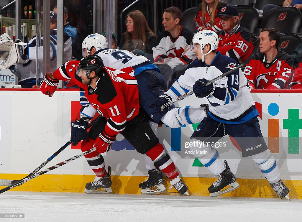 Andrew Copp #9 Nicolas Petan #19 of the Winnipeg Jets and Stephen Gionta #11 of the New Jersey Devils come together at the boards during the game at the Prudential Center on October 9, 2015 in Newark, New Jersey.
