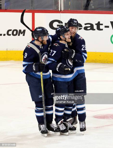 Andrew Copp Nikolaj Ehlers and Patrik Laine of the Winnipeg Jets celebrate a third period goal against the Colorado Avalanche at the Bell MTS Place...