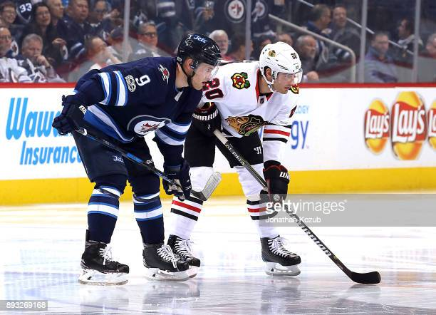 Andrew Copp of the Winnipeg Jets and Brandon Saad of the Chicago Blackhawks gets set during a third period faceoff at the Bell MTS Place on December...