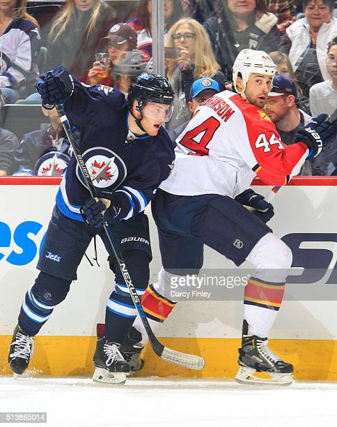 Andrew Copp of the Winnipeg Jets and Erik Gudbranson of the Florida Panthers keep an eye on the play during first period action at the MTS Centre on...