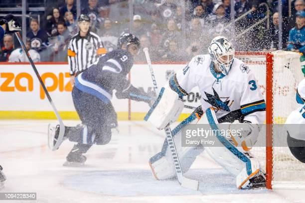 Andrew Copp of the Winnipeg Jets and goaltender Martin Jones of the San Jose Sharks keep an eye on the play during first period action at the Bell...