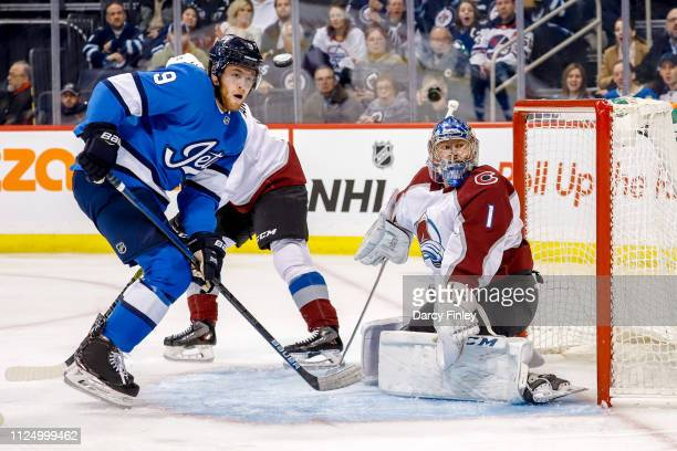 Andrew Copp of the Winnipeg Jets and goaltender Semyon Varlamov of the Colorado Avalanche eye the flying puck during first period action at the Bell...