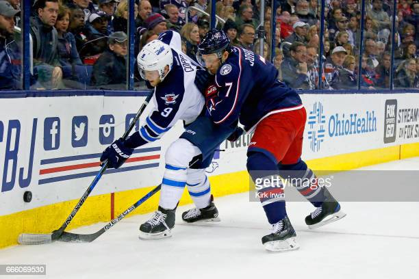Andrew Copp of the Winnipeg Jets and Jack Johnson of the Columbus Blue Jackets battle for control of the puck during the game on April 6 2017 at...