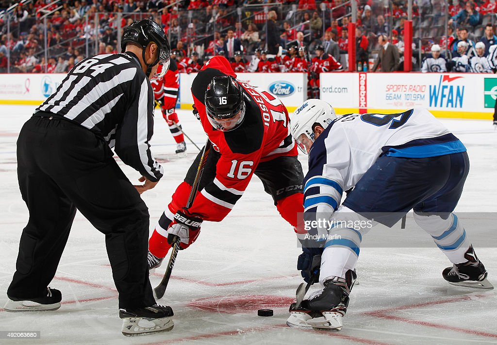 Andrew Copp #9 of the Winnipeg Jets and Jacob Josefson #16 of the New Jersey Devils face off during the game at the Prudential Center on October 9, 2015 in Newark, New Jersey.