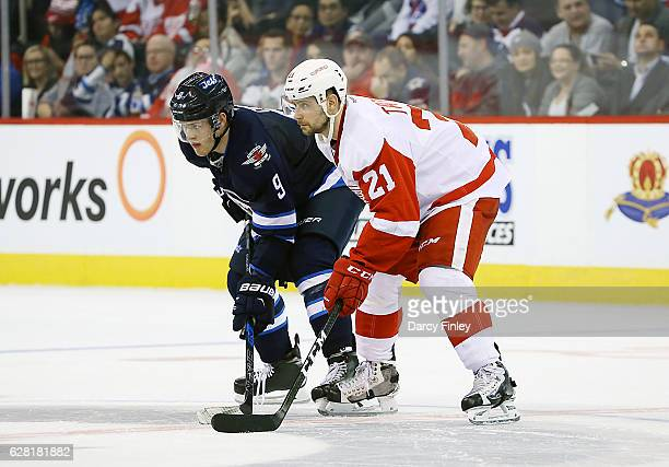 Andrew Copp of the Winnipeg Jets and Tomas Tatar of the Detroit Red Wings get set for a third period faceoff at the MTS Centre on December 6 2016 in...