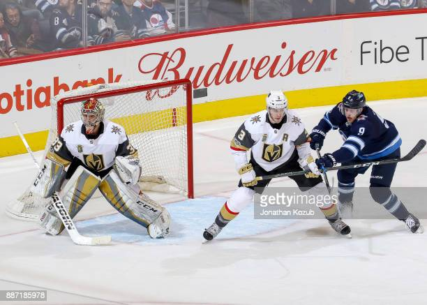 Andrew Copp of the Winnipeg Jets battles Brayden McNabb of the Vegas Golden Knights as goaltender Maxime Lagace guards the net during third period...