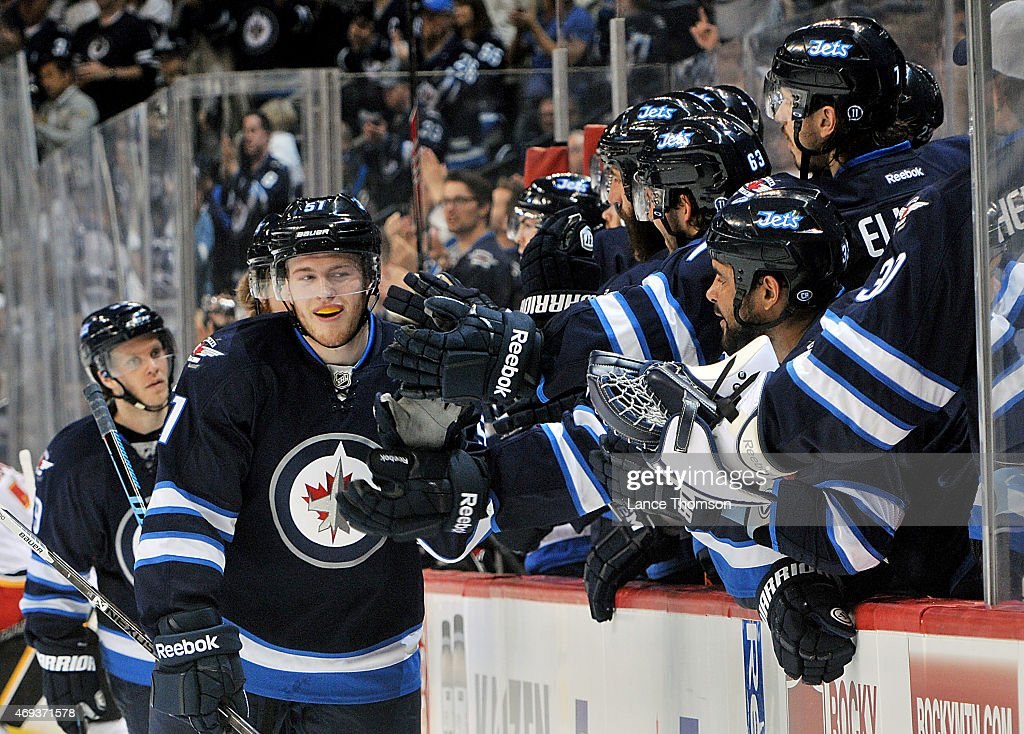 Andrew Copp #51 of the Winnipeg Jets celebrates a third period goal against the Calgary Flames with teammates at the bench on April 11, 2015 at the MTS Centre in Winnipeg, Manitoba, Canada. Copp recorded his first NHL point with an assist on the goal.