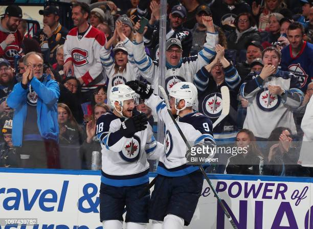 Andrew Copp of the Winnipeg Jets celebrates his second period goal against the Buffalo Sabres with Bryan Little during an NHL game on February 10...