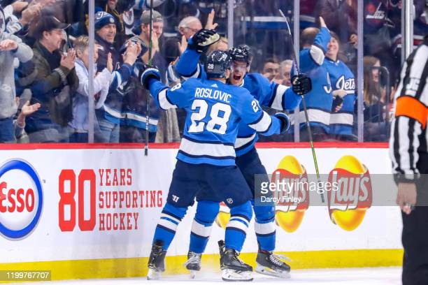 Andrew Copp of the Winnipeg Jets celebrates his third period goal against the Chicago Blackhawks with teammate Jack Roslovic at the Bell MTS Place on...