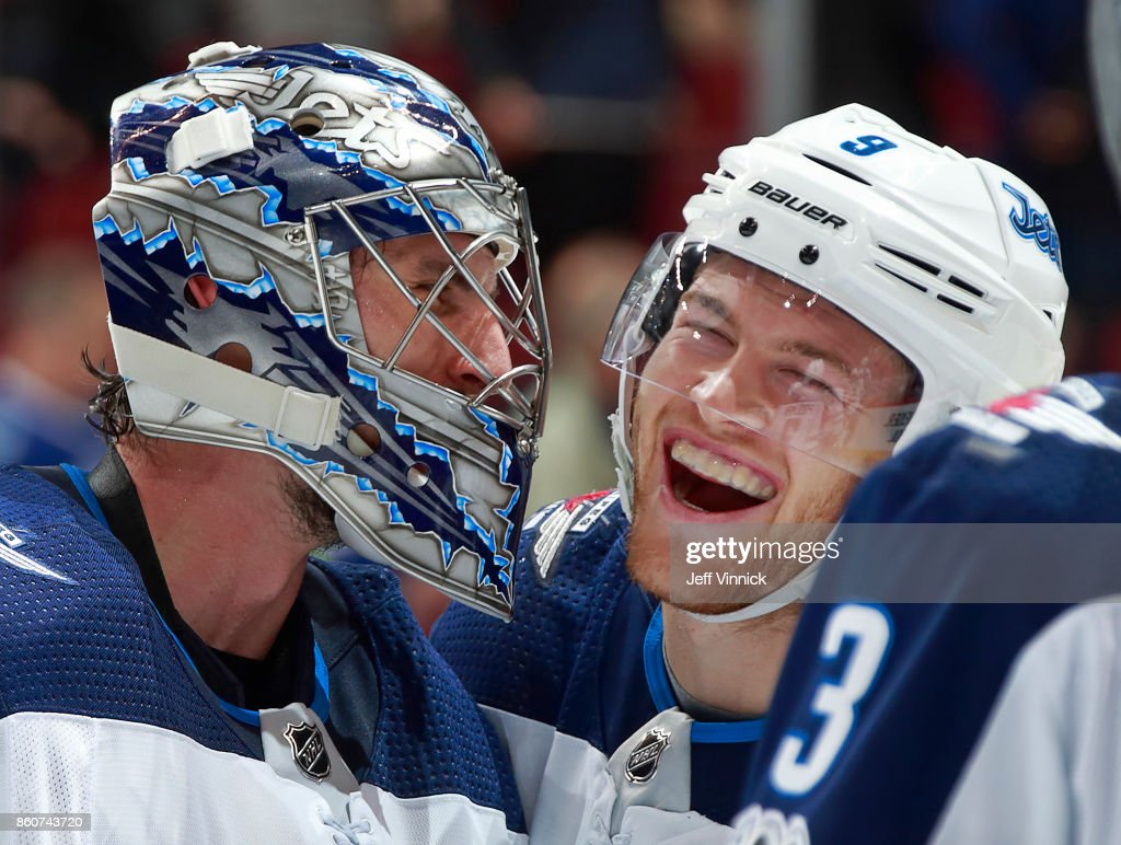 Andrew Copp #9 of the Winnipeg Jets congratulates teammate Connor Hellebuyck #37 after their NHL game against the Vancouver Canucks at Rogers Arena October 12, 2017 in Vancouver, British Columbia, Canada. The final score was 4-2 for the Winnipeg Jets.