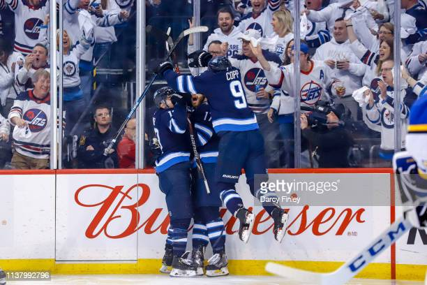 Andrew Copp of the Winnipeg Jets leaps on teammates Brandon Tanev and Adam Lowry as they celebrate a first period goal against the St Louis Blues in...