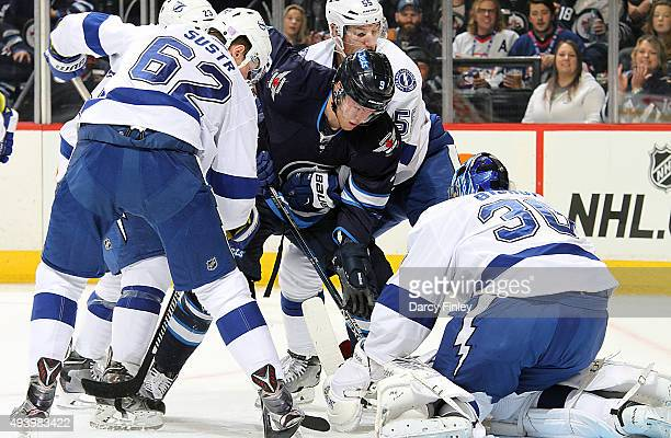 Andrew Copp of the Winnipeg Jets looks for a rebound among Tampa Bay Lightning players as goaltender Ben Bishop covers up the puck during first...