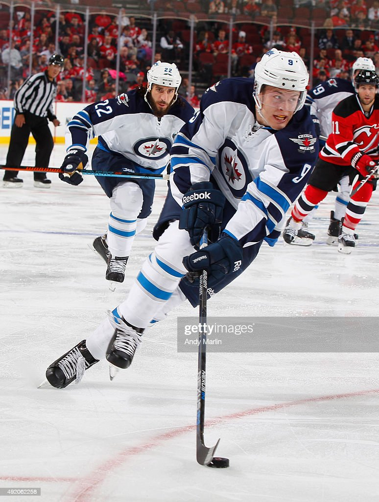Andrew Copp #9 of the Winnipeg Jets plays the puck against the New Jersey Devils at the Prudential Center on October 9, 2015 in Newark, New Jersey. The Jets defeated the Devils 3-1.