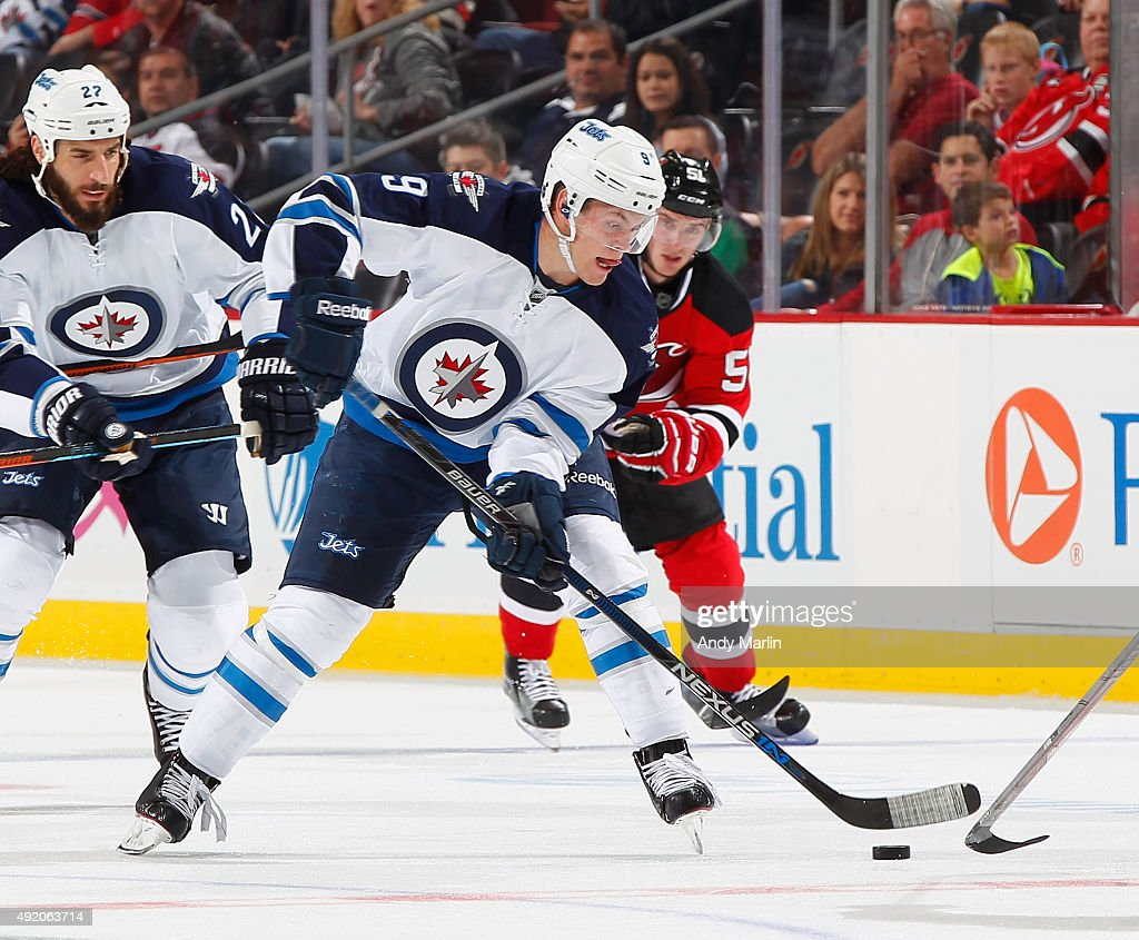 Andrew Copp #9 of the Winnipeg Jets plays the puck against the New Jersey Devils during the game at the Prudential Center on October 9, 2015 in Newark, New Jersey.