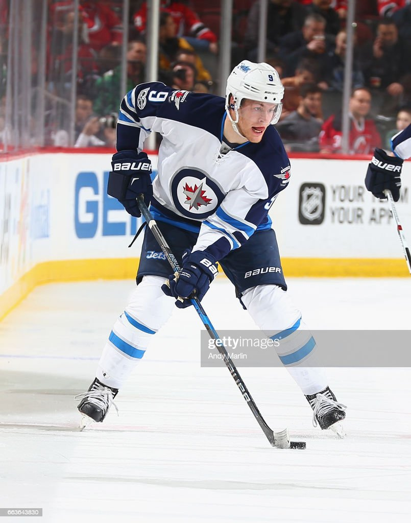 Andrew Copp #9 of the Winnipeg Jets plays the puck against the New Jersey Devils during the game at Prudential Center on March 28, 2017 in Newark, New Jersey.