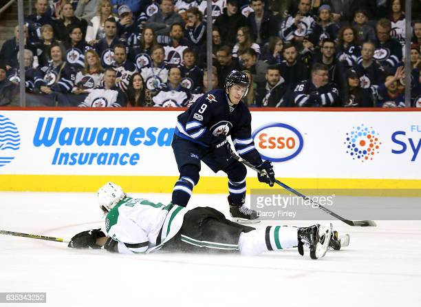 Andrew Copp of the Winnipeg Jets plays the puck down the ice as Jamie Oleksiak of the Dallas Stars slides to block the pass during first period...