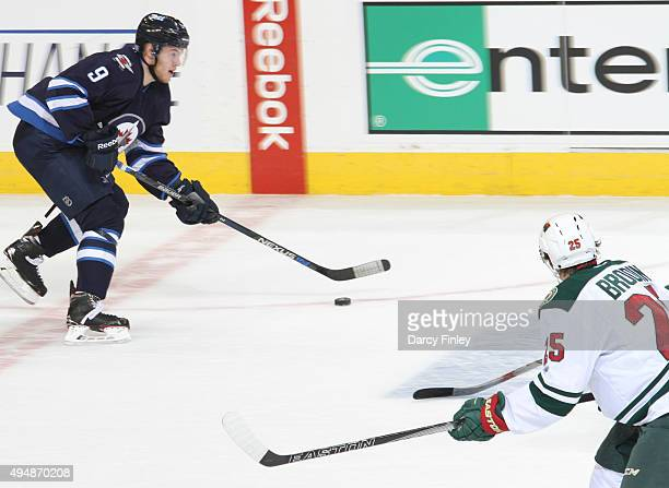 Andrew Copp of the Winnipeg Jets plays the puck up the ice as Jonas Brodin of the Minnesota Wild defends during first period action at the MTS Centre...