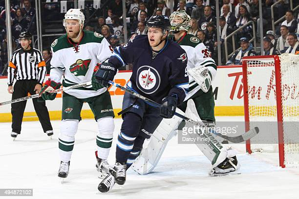Andrew Copp of the Winnipeg Jets skates in front of Christian Folin and goaltender Darcy Kuemper of the Minnesota Wild as they keep an eye on the...