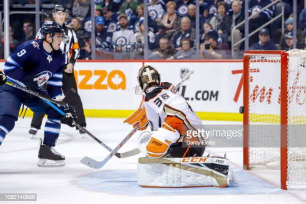 Andrew Copp of the Winnipeg Jets watches as the puck flies into the net behind goaltender John Gibson of the Anaheim Ducks for a third period goal by...