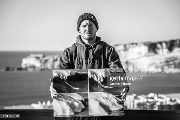 Andrew Cotton poses for a photograph holding the sequence of images of the wave that he surfed on November 8th at Praia do Norte at Nazare where he...